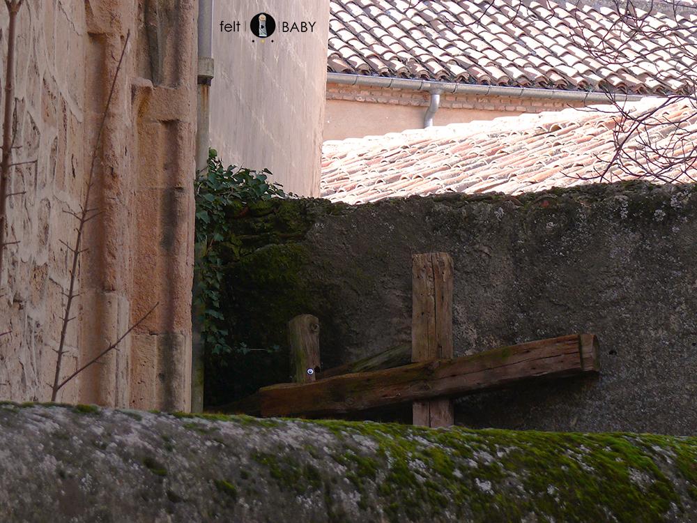Cruces de madera apoyadas en una pared de piedra con musgo